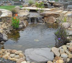 Water feature includes pond, boulders and natural stone.