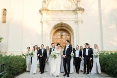 classic and elegant wedding party at the entrance to historic knowles chapel at rollins college. groom and groomsmen in black tuxedos and bridesmaids in pale grey gowns. lush flowers are all white with greenery. Elegant Wedding, Floral Wedding, Perfect Wedding, Wedding Day, Groom Attire, Groom And Groomsmen, Grey Gown, Bridesmaid Dresses, Wedding Dresses