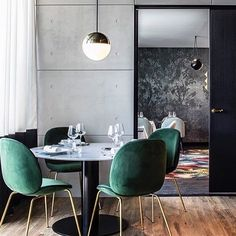 Emerald velvet chairs with concrete, brass and black details, so good! Can't get enough of this moody combo by @claude_cartier_decoration #rg @gubiofficial