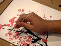 Paint your own cherry blossom tree with black and pink paint, a straw and a paintbrush.