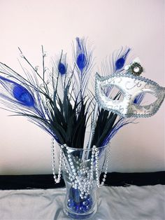 Fantastic Masquerade Party Centerpiece: feathers, mask, beads, etc http://www.mybigdaycompany.com/masquerade-ball.html