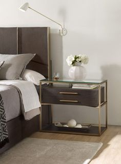 This chic wooden nightstand with a brass frame will look great in any contemporary bedroom. Featuring one drawer for storage and an elegant glass surface, this piece is the perfect addition to a modern home design.
