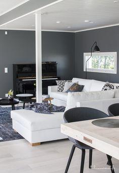 Een hoekbank tegen een grijze geverfde wand. Door het wit en de lichte vloer heeft men hier prima met een donkere kleur op de wand kunnen werken.  Meer wooninspiratie op mijn interieurblog http://www.interieurinspiratie.nl/