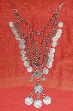 A silver chin-chain (called 'iznaq') with many coins and a cross-shaped pendant. 19th c. A museum piece of Palestinian history from the Bethlehem region.