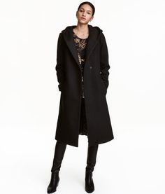 Black. Coat in a felted wool blend with a hood. Concealed snap fasteners at front, side pockets, tie belt at waist, and vent at back. Lined. Wool content is