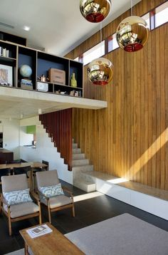 Wood paneling and retro light fixtures in this Australia home from Klopper and Davis Architects.