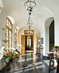 A flood of natural light comes in through the windows and French doors during the day, while bell jar lanterns illuminate the foyer in the evening.
