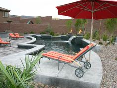 A grey stone patio and pool with water and fire features make for an exciting outdoor space. Orange striped outdoor-furniture cushions and shade umbrella, rock garden and gray pavers complete the sleek outdoor design.