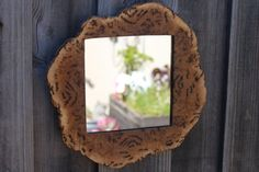 """Hand carved in our back shed from a Gimlett burl and MDF support board, this mirror will bring a little splash of the Australian bush into your space. Measuring 31 cm long x 30.5 cm wide x 1.2 cm high (12.6"""" x 12.2"""" x 0.6""""), the mirror was carved in-line with its unique, organic shape. The spikey outside finish of the mirror has been left as nature intended it, whilst the 1,200 grit sanded frame is finished with a beeswax coating, making the burl's pattern just pop! When making all our items…"""