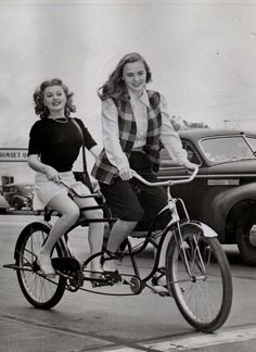 """Tumblr: ridesabike Suzi Crandall and Leza Holland ride a bike. NOTHING CAN STOP 'EM — HOLLYWOOD, CALIF. Warner Bros' actresses Leza Holland and Suzi Crandall took the Los Angeles transportation strike in stride. The two girls, who usually ride the bus to work in the morning, hired a two-seater tandem and bicycled 12 miles from Beverly Hills to the studio. They arrived in time for their first scene in """"Stallion Road."""" Acme 5/3/46"""