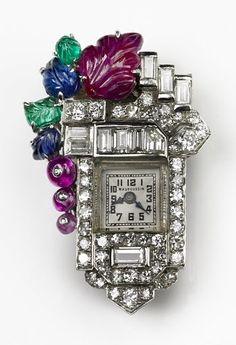 French Art DecoLapel Watch: rubies, emeralds, sapphires and diamonds, in platinum, circa 1930.