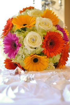 Hot pink orange and yellow gerbera daisy with white roses and hydrangea.
