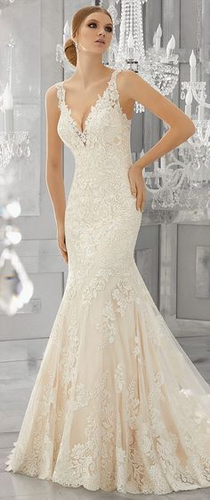 Frosted, embroidered lace appliqués accent the bodice and wide scalloped hemline on this fit and flare wedding dress. A deep v-neckline and removable diamond beaded organza belt complete the look.