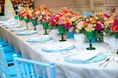 Bright and cheery tablescape with green stemware, blue glass plates, colorful floral centerpiece , Blue #chiavari chairs