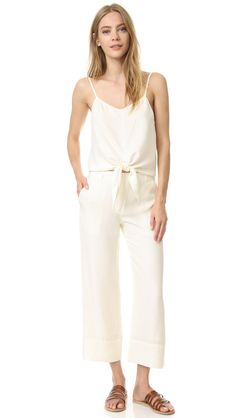 Luxe silk Jenni Kayne pants in a cropped, wide-leg profile. Topstitched cuffs. Slant front pockets and welt back pockets. Hook and eye closure and zip fly.
