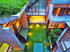 Residence in Bangladesh.  The square, concrete envelop adopts an introverted design.  With taller buildings surrounding the house, the pool and natural elements are placed inside the courtyard for privacy.  From the outside, no one can see the emerald pool and ghat.  http://archpresspk.com/new-version/sa-residency.html
