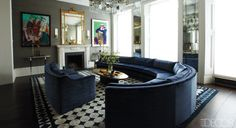 Elle Decor-The drawing room of designer Peter Mikic and TV producer Sebastian Scott's London townhouse includes a pastel by Paula Rego, left, and a print by David Hockney; the mirrored tiles are by the Looking Glass of Bath. The sofas are upholstered in a Romo velvet, the midcentury cocktail table is French, and the light fixture, consoles, silk wall covering, and rug are custom made.