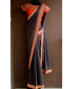 Deep grey sari mirror embroidery on border   1. Deep grey chiffon embroidered saree2. Deep grey pure chiffon saree with orange mirror work border3. Comes with stitched blouse