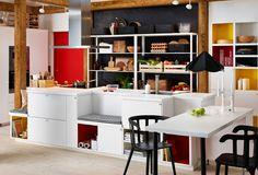 Vy av hela köket med köksö, matplats och IKEA hyllor.