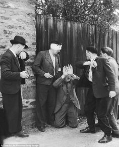Two Frenchmen train guns on a collaborator who kneels against a wooden fence with his hands raise while another cocks an arm to hit him, Rennes, France, in late August 1944