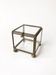 "Vintage brass and glass jewelry box with pedestal feet. This glass trinket box has a lid on top that opens, closes, and latches shut. A perfect small box to use as a ringbearer box or to photograph small accessories or jewelry on the wedding day. Would also make a great piece to include in a proposal!  {Condition} Item is in great vintage condition.  {Dimensions} ♡ Box width: 2 1/4"" ♡ Box length: 2 1/4"" ♡ Box height {including feet}: 2 1/4"" ♡ Depth of Box {inside depth}: 1 3/4""  {Other…"