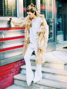 Maja Wyh wears layered t-shirt, a fur coat, and flares