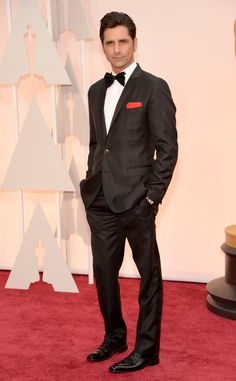 John Stamos from Best Dressed Men at the 2015 Oscars  In a suave black tux with a crimson pocket square