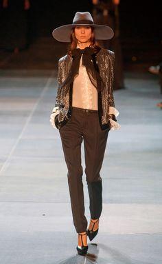 Dos tonos opuestos que te atraerán seguro. ¿A qué esperas para duarte? Yves Saint Laurent Con un toque dandy, chaqueta brillante, camisas blanca y pantalones sastre, de Yves Saint Laurent.
