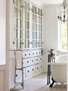 Vintage bathroom with claw foot tub, crystal chandelier and built-in white glass-front cabinets and white built-in apothecary chests.
