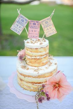 This wedding cake takes exposed layers to the next level by topping them off with vintage tickets. Photo by Cambria Grace via Style Me Pretty