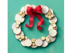 """Hot-glue 3"""" birch wood coasters ($16 for 20; rachaelsscraps.etsy.com) side by side to form a wreath shape. Add a mix of 3"""" and ¾"""" slices ($6 for 25; factorydirectcraft.com) atop each joint. Finish with ribbon for a pop of color."""
