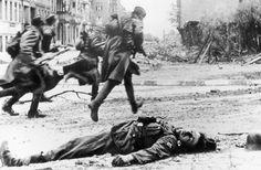 70 anos do fim da Segunda Guerra Mundial Legenda: Soldados correm em meio ao escombros e corpos durante a batalha para o controle da cidade de Berlim (Ivan Shagin/Getty Images)