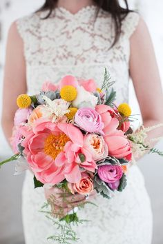 Bright bouquet of peonies, ranunculi, roses, and billy buttons