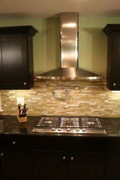 Great look for the kitchen.  Tile backsplash with pot filler, black countertops and black Mocha Shaker cabinets.