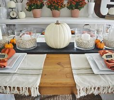 If you're not into the idea of dressing your dining table in a super dramatic and moody theme, create a fall-inspired look that could last you through Thanksgiving. The centerpiece is easy to put together with pumpkins and large candles placed in glass cylinders. Each place setting is simple—a dishtowel serves as a placemat and white plates are topped with orange napkins.