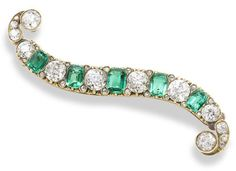 A late 19th century emerald and diamond brooch, circa 1890  The S-shaped scroll alternately set with old brilliant-cut diamonds and step-cut emeralds and rose-cut diamond highlights, diamonds approximately 3.90 carats total, length 6.2cm.