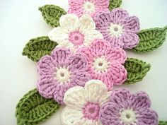 Spring Crochet flowers with leaves.  Would make a great table runner if you make it long enough