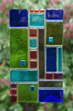 Beautiful contemporary green, blue, red, purple sun-catcher with shimmering dichroic iridescent accents. I hand cut all the glass elements to make this one of a kind original sun-catcher. It comes with a rust-proof stainless steel chain for hanging. Perfect for adding a pop of color and design to any window or patio. It is approximately 7 x 4 inches. Please hang with a sturdy nail or hook. Do not use a plastic suction cup hook because they eventually release with disastrous results. ...