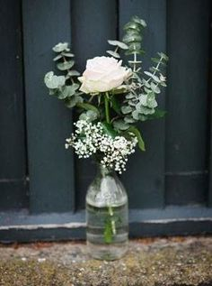 A simple wedding centerpiece with eucalyptus, white rose and baby's breath.