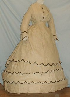 """1865 two piece tan linen dress. Dress has separate overskirt.  Front of bodice & sleeve cuffs trimmed with black silk appliques.  Sleeve cuffs and lower hem also trimmed with black cotton braiding.  Neck, armscyes & waist are piped.  Bodice unlined and has front hook & loop closure.  Skirt unlined except wide band of cotton at hemline.  Overskirt has bustle back and trimmed with black cotton braiding.  Bust: 34""""; Waist: 26""""; Front skirt length: 40""""; Back length: 43""""."""