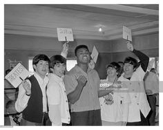 American heavyweight boxer Cassius Clay (later Muhammad Ali) in a boxing ring with the Beatles at the 5th Street Gym, Miami, during the run-up to his title fight against Sonny Liston, 18th February 1964. The Beatles are holding up cards describing Clay as: 'Greatest', '218 lbs', 6', 3''' and '22 yrs'. Left to right: Paul McCartney, George Harrison (1943 - 2001), Clay, Ringo Starr and John Lennon (1940 - 1980).