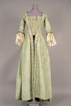 green moire Robe à la Française, probably English, circa 1770. With narrow sack back pleats, box pleated sleeve ruffles, silver metal edging on ruched self robings, and on bodice front, lace at sleeves later addition. Doyle New York
