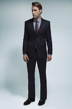Costume azul marinho, camisa acetinada com aspecto denim, gravata bordô com micro-poá e calçado inglês café.