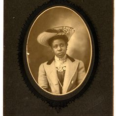 """African American Woman 1890s """"Woman, head and shoulders, wearing a light colored wool coat over a dark, high collared dress and large hat"""""""