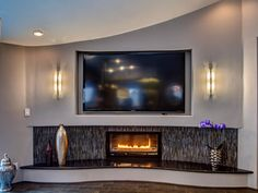 The shiny mosaic tile combines with the black quartz and contemporary gas fireplace to give this stunning living room a touch of glam.