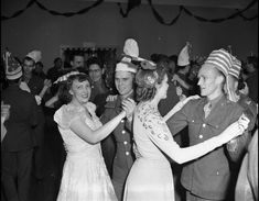 A crowd of military personnel and civilians gather at a U.S.O. club to celebrate New Year's Eve on December 31, 1942.