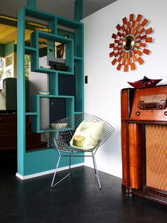 Bertoia chair in entry This is a very cool little corner with a Bertoia chair, turquoise room divider and sunburst-like wall decoration.This is a very cool little corner with a Bertoia chair, turquoise room divider and sunburst-like wall decoration. Casa Retro, Retro Home, Mid Century Decor, Mid Century Furniture, Midcentury Modern, Wooden Room Dividers, Wall Dividers, Room Divider Shelves, Divider Cabinet