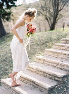 a film photograph of a bride walking through memorial park in salt lake city on her wedding day holding a bouquet by ashley beyer of tinge