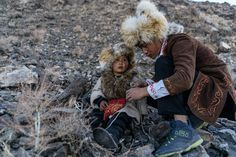 Bazarbai Dinismal, 4, a hunter in training, with a relative at the festival. Falcons, like the one pictured here, are also used in the hunt.Credit - Hannah Reyes Morales for The New York Times