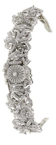 A diamond-set tiara/wristwatch, circa 1960 The openwork bracelet of swirling ribbon design with a concealed watch at the centre, accompanied by a frame to convert into a tiara, two diamonds deficient, dial and movement signed Cyma, bracelet length 19.5cm. Image Bonhams. http://www.bonhams.com/auctions/22629/lot/277/